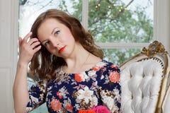 Una chica joven hermosa en un vestido colorido brillante se sienta en una silla cerca de la ventana y ajusta su pelo Azul hermoso Foto de archivo libre de regalías