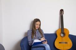 Una chica joven hermosa escribe canciones foto de archivo libre de regalías
