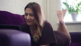 Una chica joven hermosa está mintiendo en el sofá y goza de una tableta que se mueve las piernas HD Estilo casero metrajes