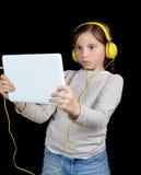 Una chica joven hermosa que escucha la música con una tableta digital Imágenes de archivo libres de regalías