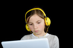 Una chica joven hermosa que escucha la música con una tableta digital Fotos de archivo