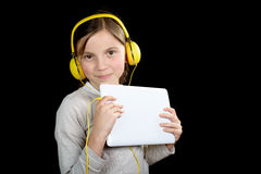 Una chica joven hermosa que escucha la música con una tableta digital Foto de archivo