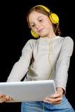 Una chica joven hermosa que escucha la música con una tableta digital Imagenes de archivo