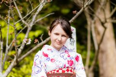 Una chica joven hermosa que mira en la cámara que lleva un kimono Fotografía de archivo libre de regalías