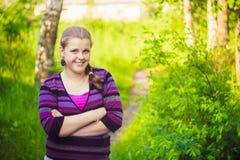 Una chica joven hermosa que se coloca en Forest Path Road Foto de archivo