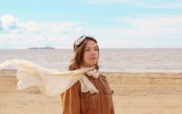Una chica joven hermosa se coloca en la orilla de la bahía en la ropa experimental del ` s con un vuelo de la bufanda en el vient Fotos de archivo