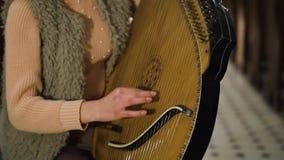Una chica joven juega en un bandura ucraniano tradicional del instrumento en la iglesia almacen de metraje de vídeo