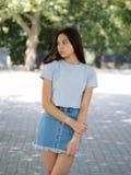 Una chica joven linda en ropa casual en un fondo borroso natural Concepto urbano, de la moda y de la juventud Copie el espacio Fotos de archivo