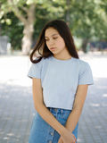 Una chica joven linda en ropa casual en un fondo borroso natural Concepto urbano, de la moda y de la juventud Copie el espacio Imagenes de archivo