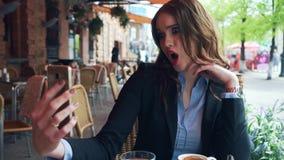Una chica joven lujosa en un traje de negocios se hace el selfie en un café almacen de video