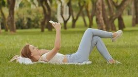 Una chica joven miente en ella detrás en la hierba verde con un smartphone en sus manos Diversión que presenta en el teléfono de  Imágenes de archivo libres de regalías