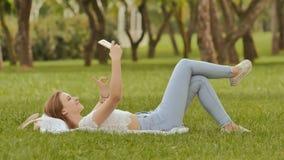 Una chica joven miente en ella detrás en la hierba verde con un smartphone en sus manos Diversión que presenta en el teléfono de  Fotos de archivo