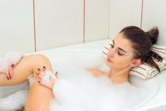 Una chica joven miente en un baño con una espuma grande y se lava los pies Imagen de archivo libre de regalías