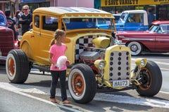 Una chica joven mira el motor de un coche de carreras de Ford Model A foto de archivo libre de regalías
