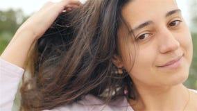 Una chica joven mira en la cámara y se endereza el pelo Sonrisa hermosa en su cara Primer A cámara lenta almacen de video