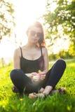 Una chica joven mira la cámara mientras que camina en el parque Foto de archivo