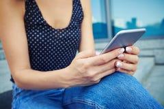 Una chica joven moderna que comprueba el correo electrónico vía el teléfono elegante Imagen de archivo