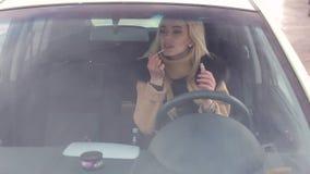 Una chica joven pinta sus labios mientras que se sienta en coche metrajes