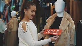 Una chica joven pone una etiqueta engomada en una cosa manicured almacen de video