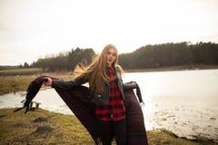 Una chica joven presenta en la orilla de un lago, lanzando una bufanda en ella imagenes de archivo
