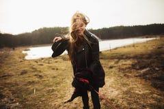 Una chica joven presenta en la orilla de un lago, lanzando una bufanda en ella fotografía de archivo