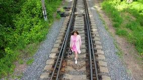 Una chica joven que camina en las pistas de ferrocarril El ir de excursi?n en el parque almacen de metraje de vídeo