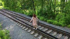 Una chica joven que camina en las pistas de ferrocarril El ir de excursi?n en el parque metrajes