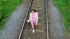 Una chica joven que camina en las pistas de ferrocarril El ir de excursi?n en el parque almacen de video