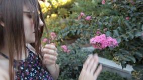 Una chica joven que caminaba en un parque del verano doblado abajo para sentir el olor de flores rosadas hermosas, el olor era de metrajes