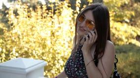Una chica joven que caminaba en un parque verde del verano decidía llamar a un amigo almacen de metraje de vídeo
