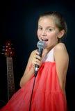 Una chica joven que canta con un micrófono Fotografía de archivo libre de regalías
