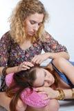 Una chica joven que conforta a su amigo Foto de archivo libre de regalías