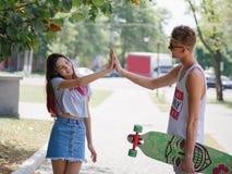 Una chica joven que da a cinco su novio lindo con un longboard en un fondo borroso del parque Relación y concepto del amor Fotos de archivo