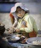 Una chica joven que descasca conchas de peregrino en Vietnam Foto de archivo libre de regalías