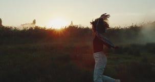 Una chica joven que gira alrededor en la hierba verde larga almacen de video