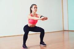 Una chica joven que hace posiciones en cuclillas en un gimnasio Mujer joven en desgaste del deporte con entrenamiento de los auri Fotos de archivo