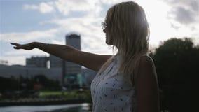 Una chica joven que intenta tocar el viento almacen de video
