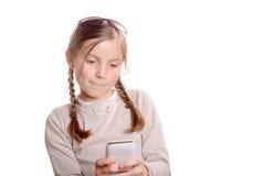 Una chica joven que juega con un teléfono móvil Imagenes de archivo