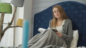 Una chica joven que lee un libro que se sienta en cama metrajes