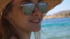 Una chica joven que lleva un sombrero y los vidrios a través de los cuales usted pueda ver el mar mira en la cámara y la sonrisa metrajes