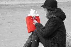 Una chica joven que lleva un sombrero y una capa se sienta en una red de pesca en la playa y mira el regalo en su mano, un rojo b Imágenes de archivo libres de regalías