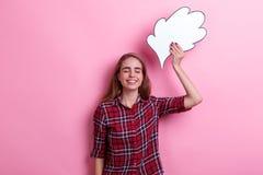 Una chica joven que llevaba a cabo una imagen de papel del pensamiento o de la idea de arriba y que sonreía con los ojos se cerró Imágenes de archivo libres de regalías