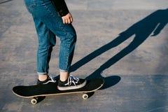 Una chica joven que monta un monopatín Fotografía de archivo