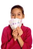Una chica joven que muestra apagado un manojo de dinero en circulación Fotografía de archivo libre de regalías
