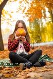 Una chica joven que oculta su cara detrás de una calabaza Fotografía de archivo libre de regalías