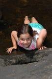 Una chica joven que pone en su estómago en un arroyo del país Fotos de archivo
