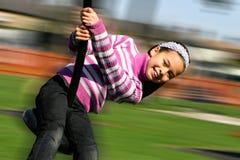 Una chica joven que ríe feliz como ella monta en el poste del patio Imagenes de archivo