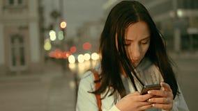 Una chica joven que se coloca en la calle de la noche y que manda un SMS en el teléfono elegante, tono del color del vintage almacen de metraje de vídeo