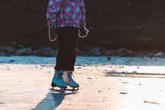 Una chica joven que se coloca en patines en una charca congelada en el hielo Fotos de archivo libres de regalías
