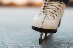 Una chica joven que se coloca en patines en una charca congelada en el hielo Fotos de archivo